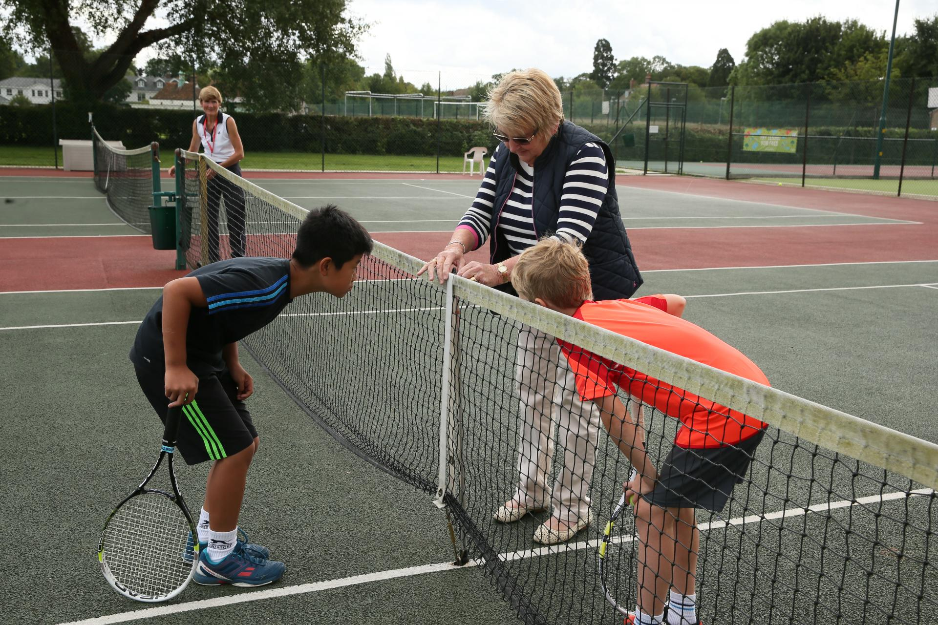 Young tennis players check net height with volunteer